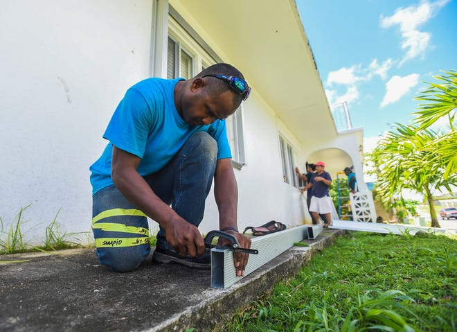 EMI Aluminum and Glass Product employee Jasper Franklin works on shutter installation at the Sinajana residence of Daniel Sablan, 75, Sept. 8, 2018.