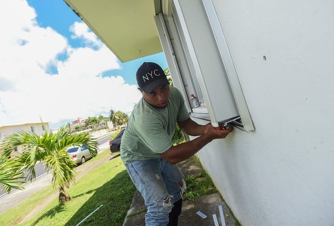 An EMI Aluminum and Glass Product employee installs shutters at the home of Daniel Sablan in Sinajana on Sept. 8, 2018.