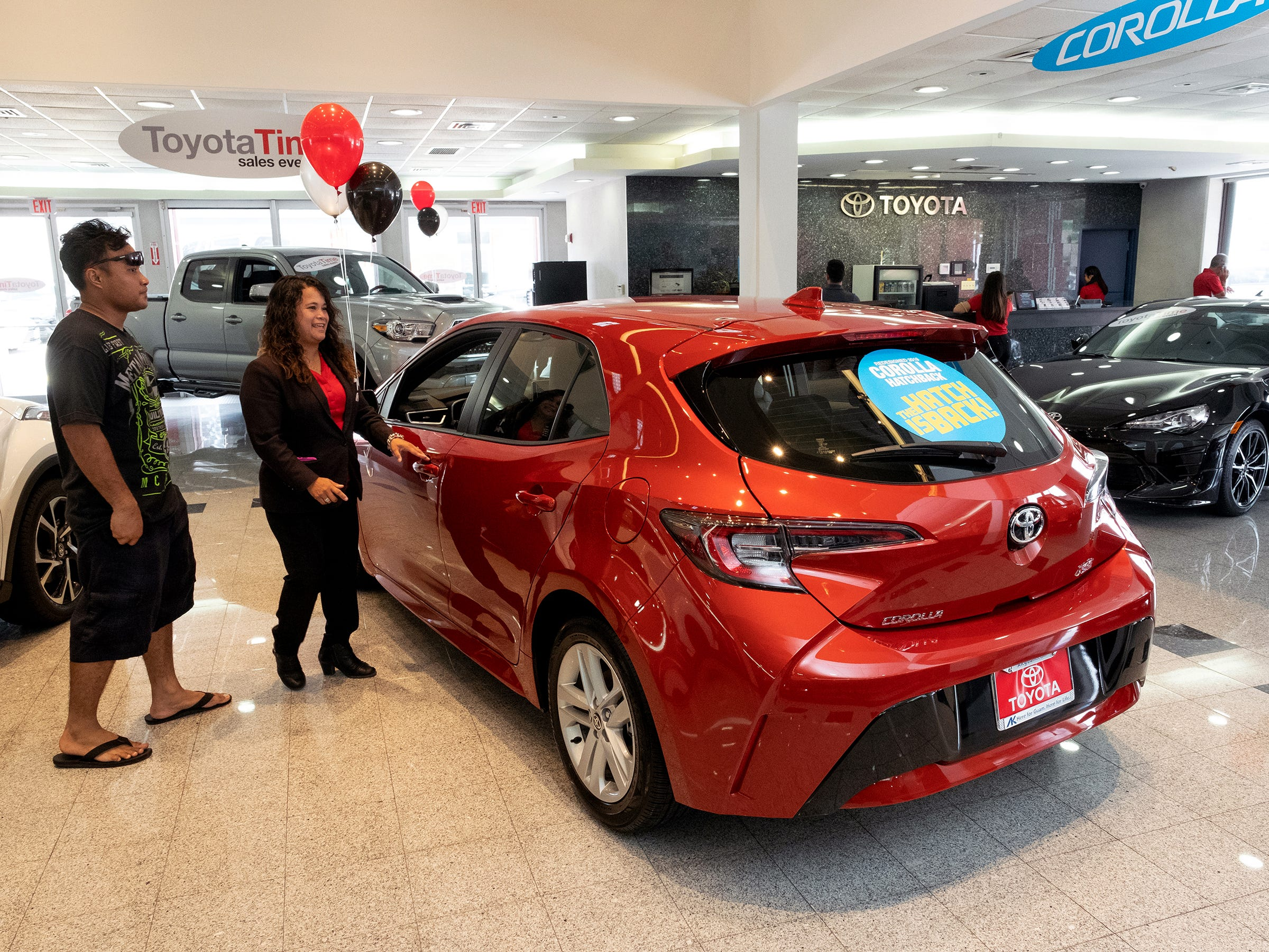 Mona Cing, a sales associate for Atkins Kroll Toyota shows the 2019 Toyota Corolla hatchback to Andrew Milfith of Tamuning in the showroom Sept. 8, 2018.