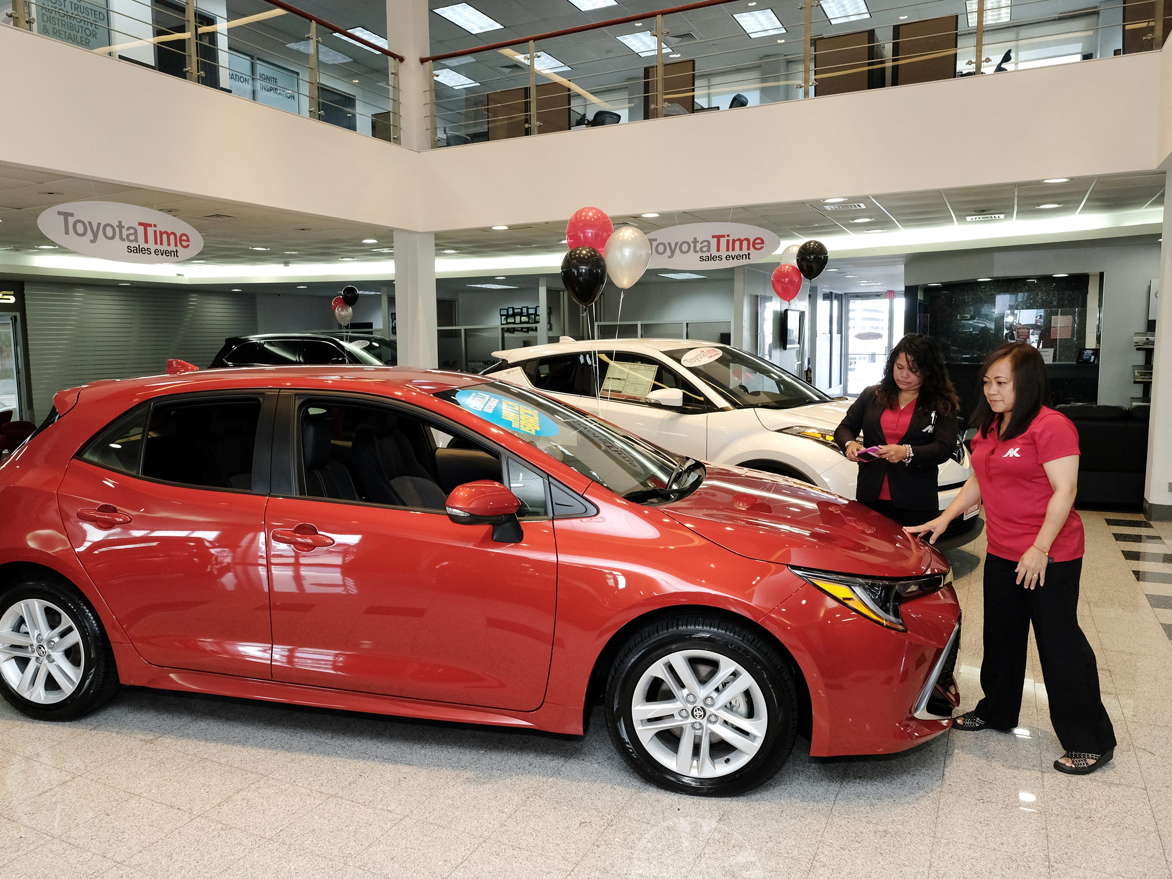 Mona Cing and Cathy Ignacio, sales associates for Atkins Kroll Toyota, show the 2019 Toyota Corolla in the showroom Sept. 8, 2018.