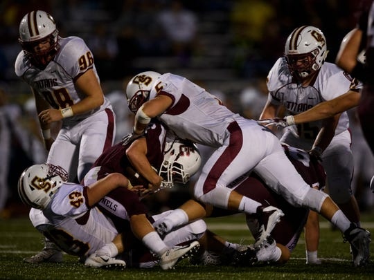 Henderson's Logan Green (6) is taken down by Gibson Southern's Logan Fauquher (43) and Garrett Martin (5) during the first quarter at Jewell Stadium in Fort Branch, Ind., Friday, Sept. 7, 2018.