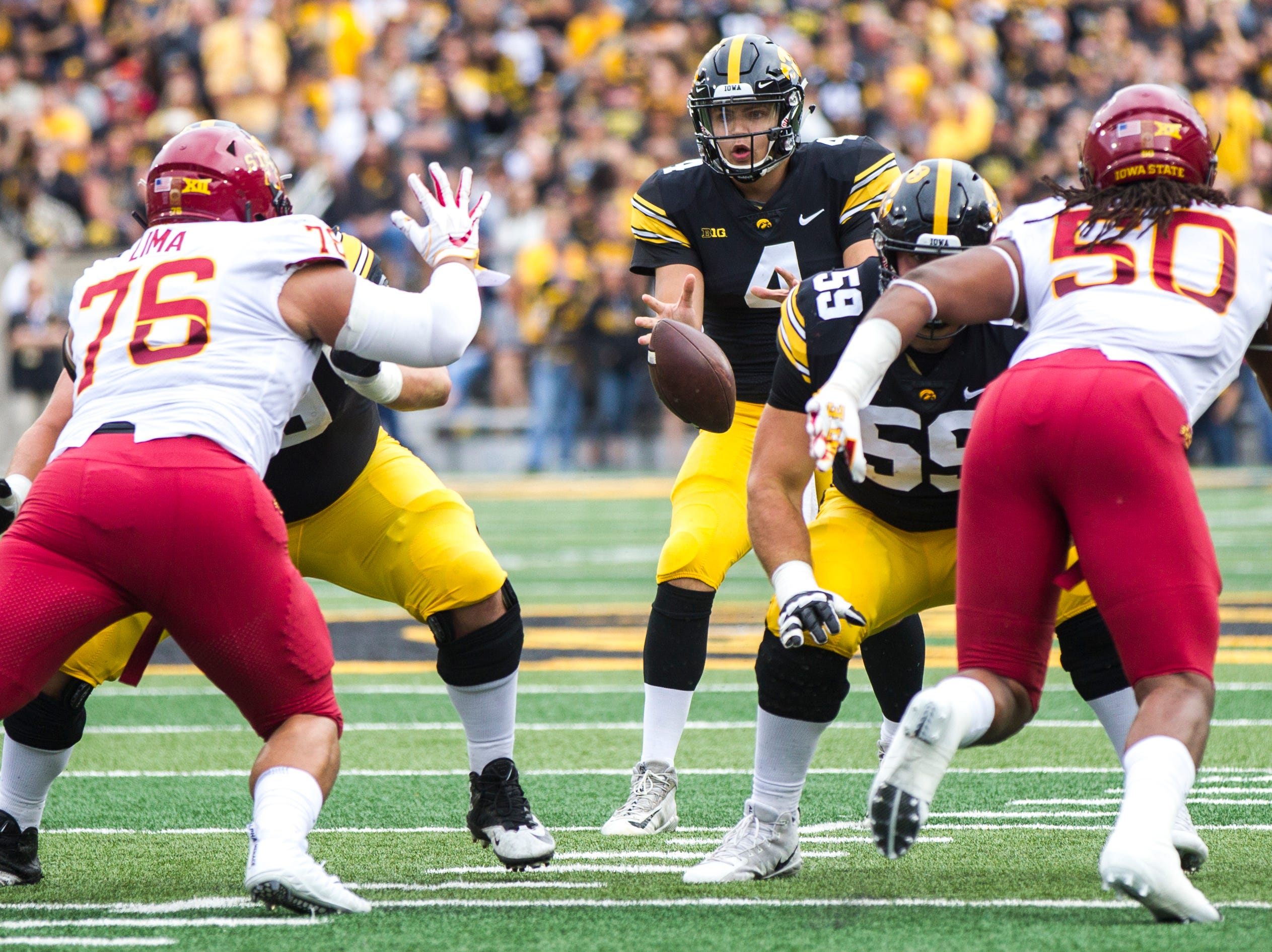 Iowa quarterback Nate Stanley (4) takes a snap from Iowa offensive lineman Keegan Render (69) during the Cy-Hawk NCAA football game on Saturday, Sept. 8, 2018, at Kinnick Stadium in Iowa City.