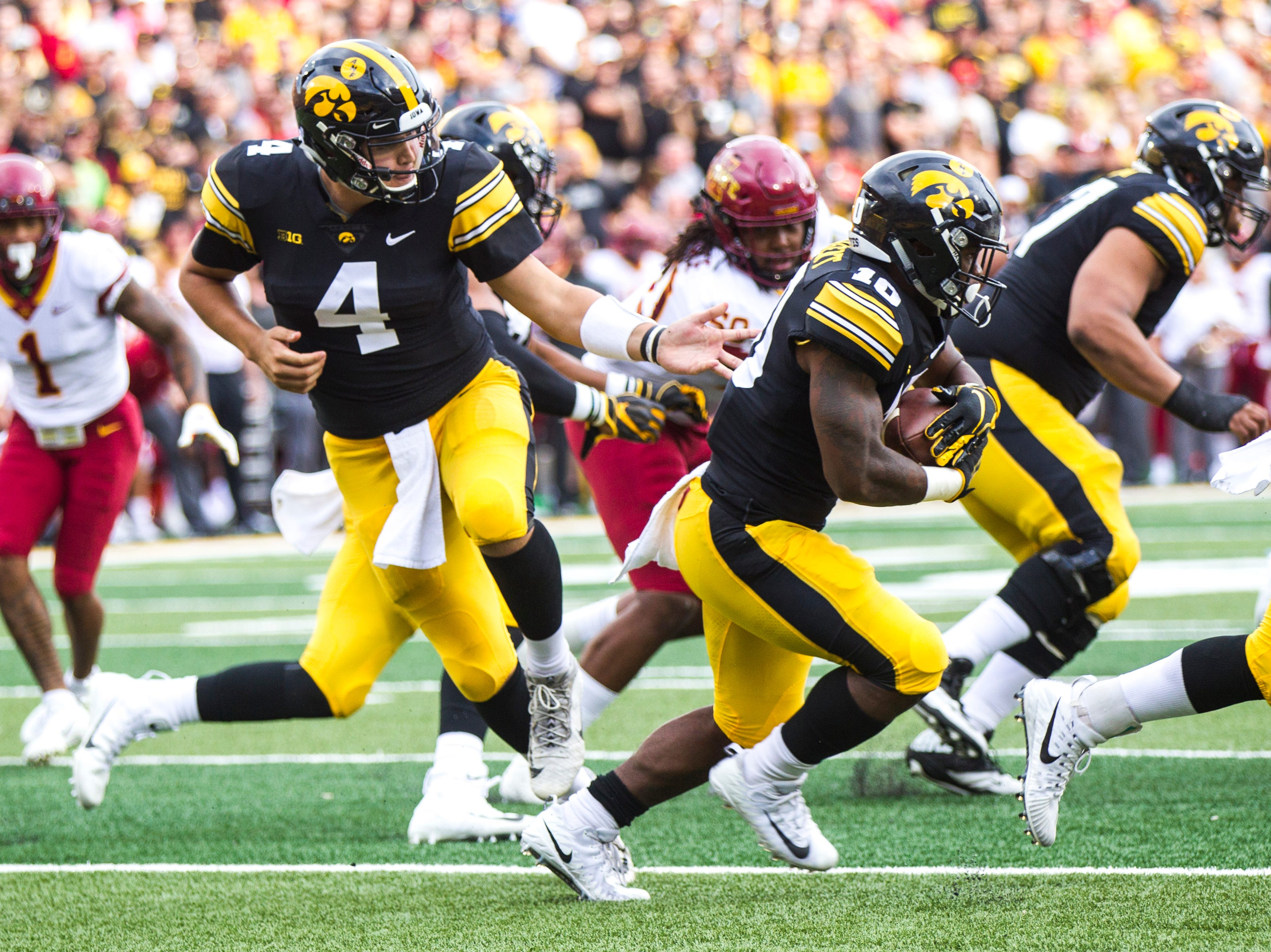 Iowa quarterback Nate Stanley (4) hands off a ball to Iowa running back Mekhi Sargent (10) during the Cy-Hawk NCAA football game on Saturday, Sept. 8, 2018, at Kinnick Stadium in Iowa City.