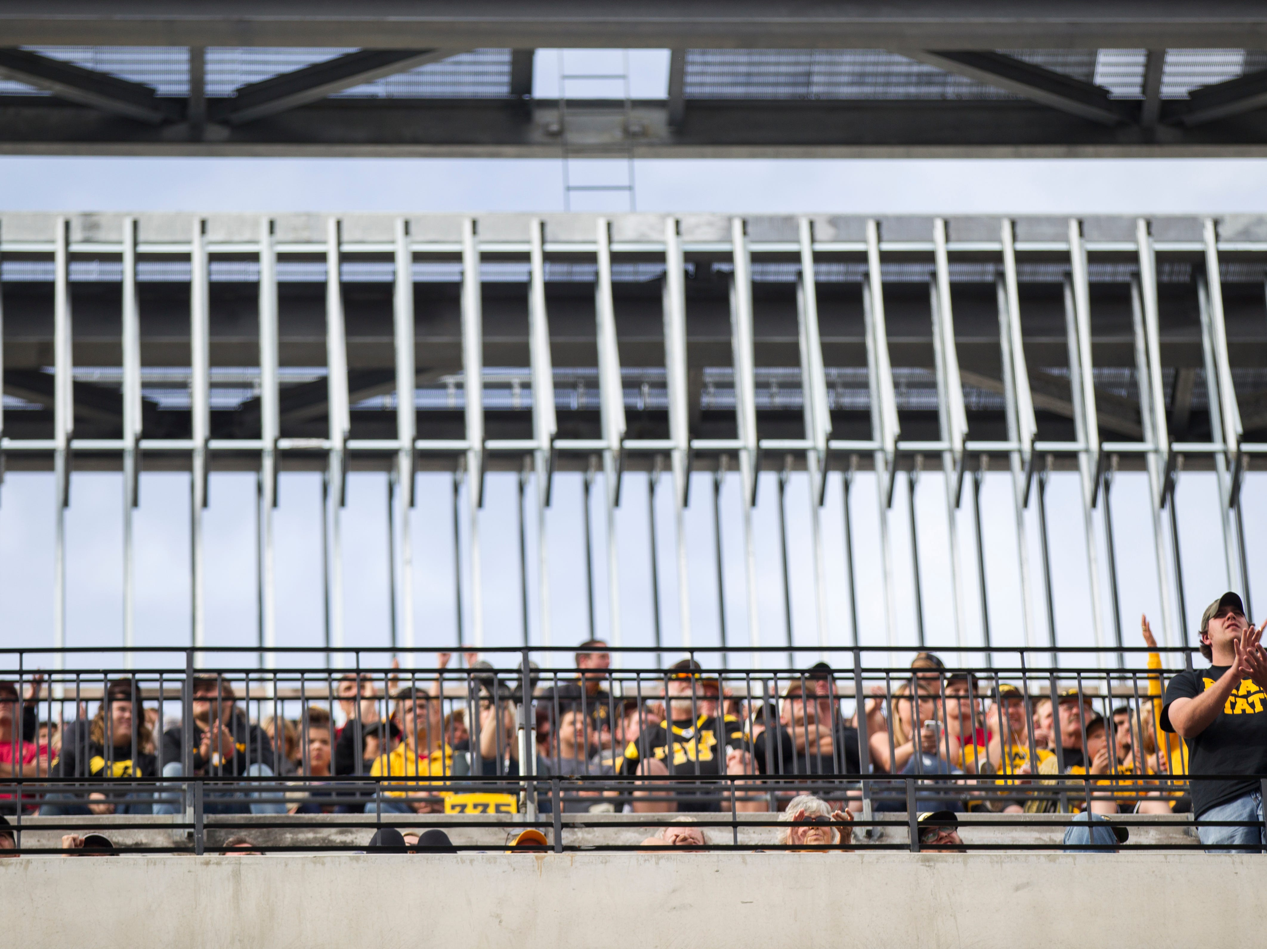 A fan in the upper deck of the north end zone cheers during the Cy-Hawk NCAA football game on Saturday, Sept. 8, 2018, at Kinnick Stadium in Iowa City.