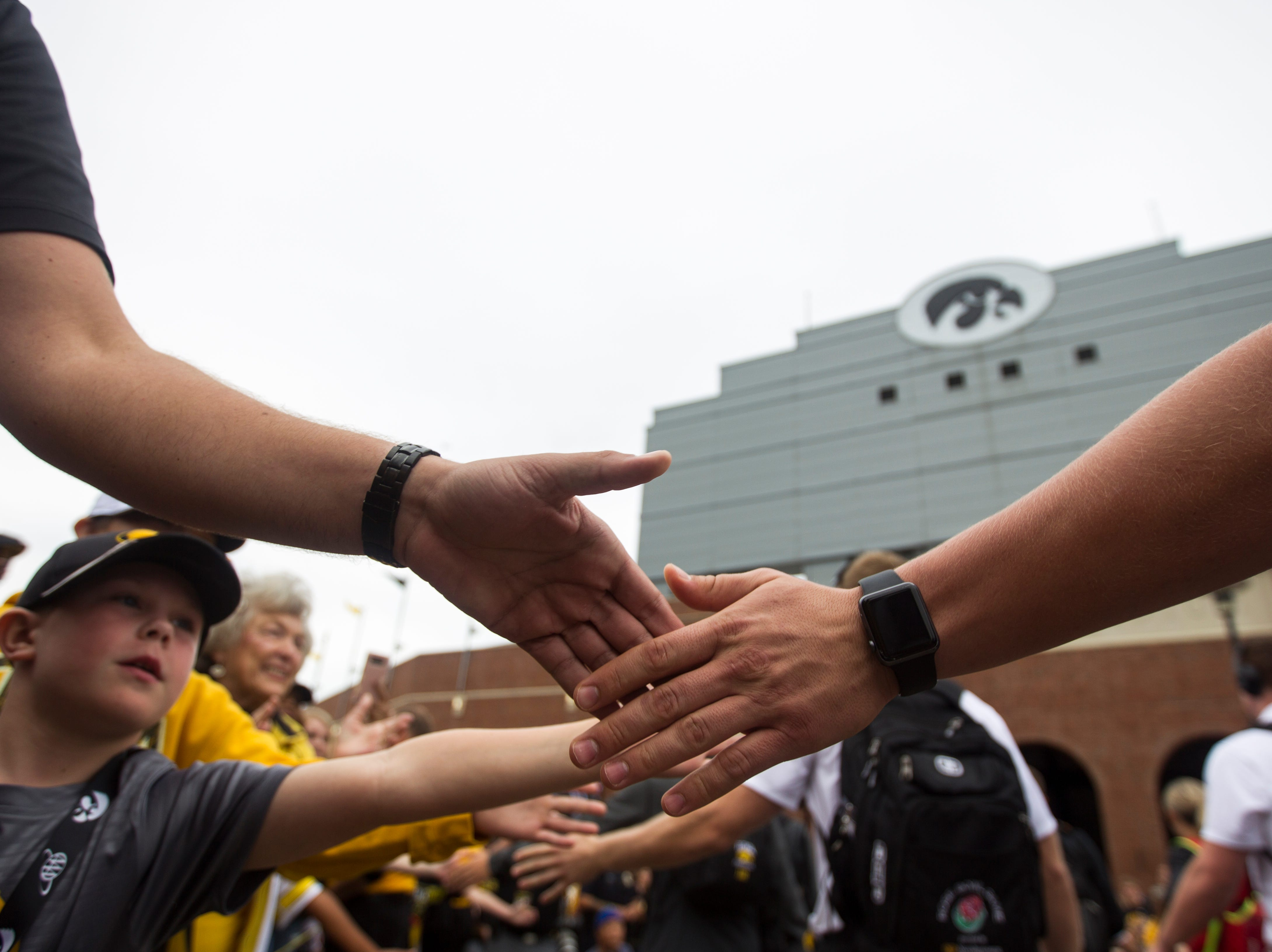 Fans high-five players as they walk into the stadium before the Cy-Hawk NCAA football game on Saturday, Sept. 8, 2018, at Kinnick Stadium in Iowa City.