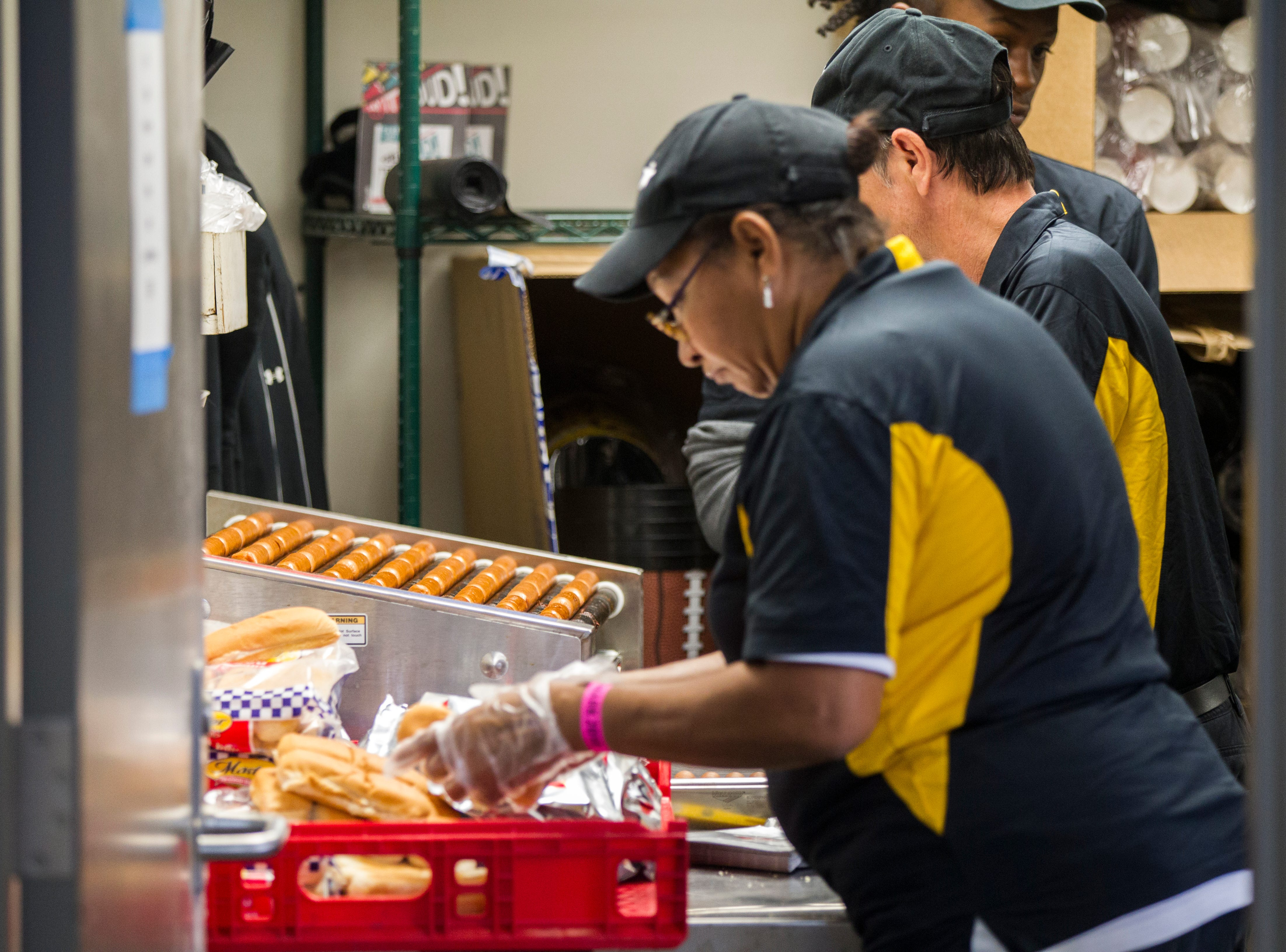 Concession workers prepare hot dogs before the Cy-Hawk NCAA football game on Saturday, Sept. 8, 2018, at Kinnick Stadium in Iowa City.