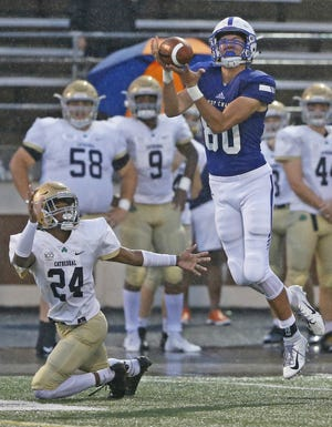 Bishop Chatard's Jack Kassenbrock completes a pass against Cathedral's Jay Jones-Moore before running the ball 72-yards for a touchdown in the first half of the game at Arsenal Tech in Indianapolis, Ind., Friday, Sept. 7, 2018. Bishop Chatard defeated Cathedral 17-14.
