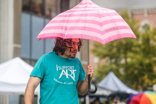 A man keeps dry under a Victoria's Secret pink umbrella during the 6th Annual Sun King CANvitational in downtown Indianapolis on Saturday, Sept. 8, 2018.
