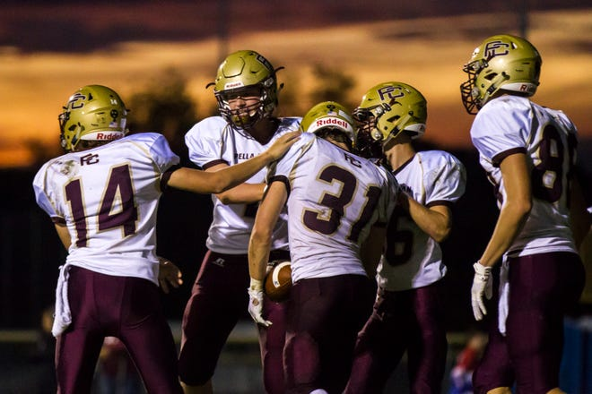 Pella Christian players celebrate with teammate Noah Treimer (31) after he scored a touchdown during a Class 1A varsity football game on Friday, Sept. 7, 2018, at Regina in Iowa City.