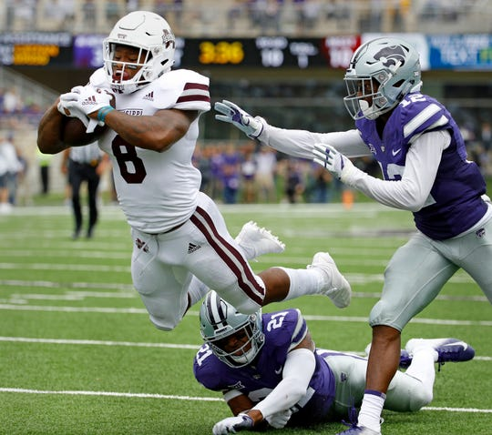 Mississippi State running back Kylin Hill (8) gets past Kansas State defensive backs AJ Parker (12) and Kendall Adams (21) to score a touchdown on a 16-yard run during the first half of an NCAA college football game Saturday, Sept. 8, 2018, in Manhattan, Kan. (AP Photo/Charlie Riedel)