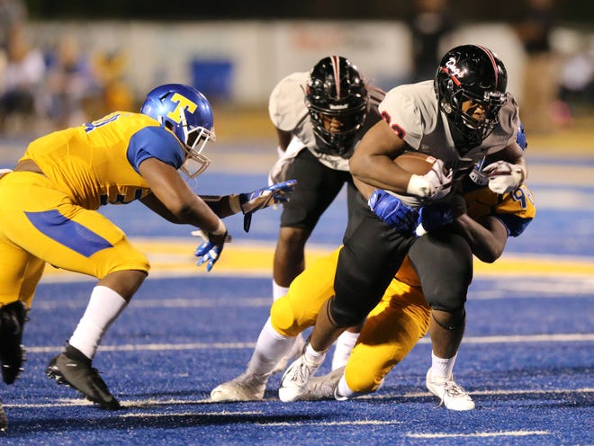 Brandon running back Dallas Smith pulls tow Tupelo defenders with him as they beat Tupelo Friday night.