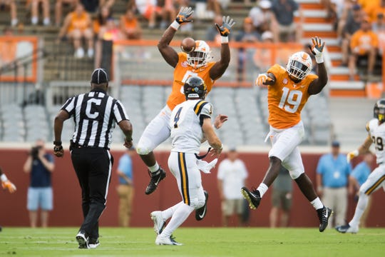 Tennessee defensive lineman Kyle Phillips (5) and Tennessee linebacker Darrell Taylor (19) defend against a pass by ETSU quarterback Logan Marchi (4) during a game between Tennessee and ETSU at Neyland Stadium in Knoxville, Tennessee on Saturday, September 8, 2018.