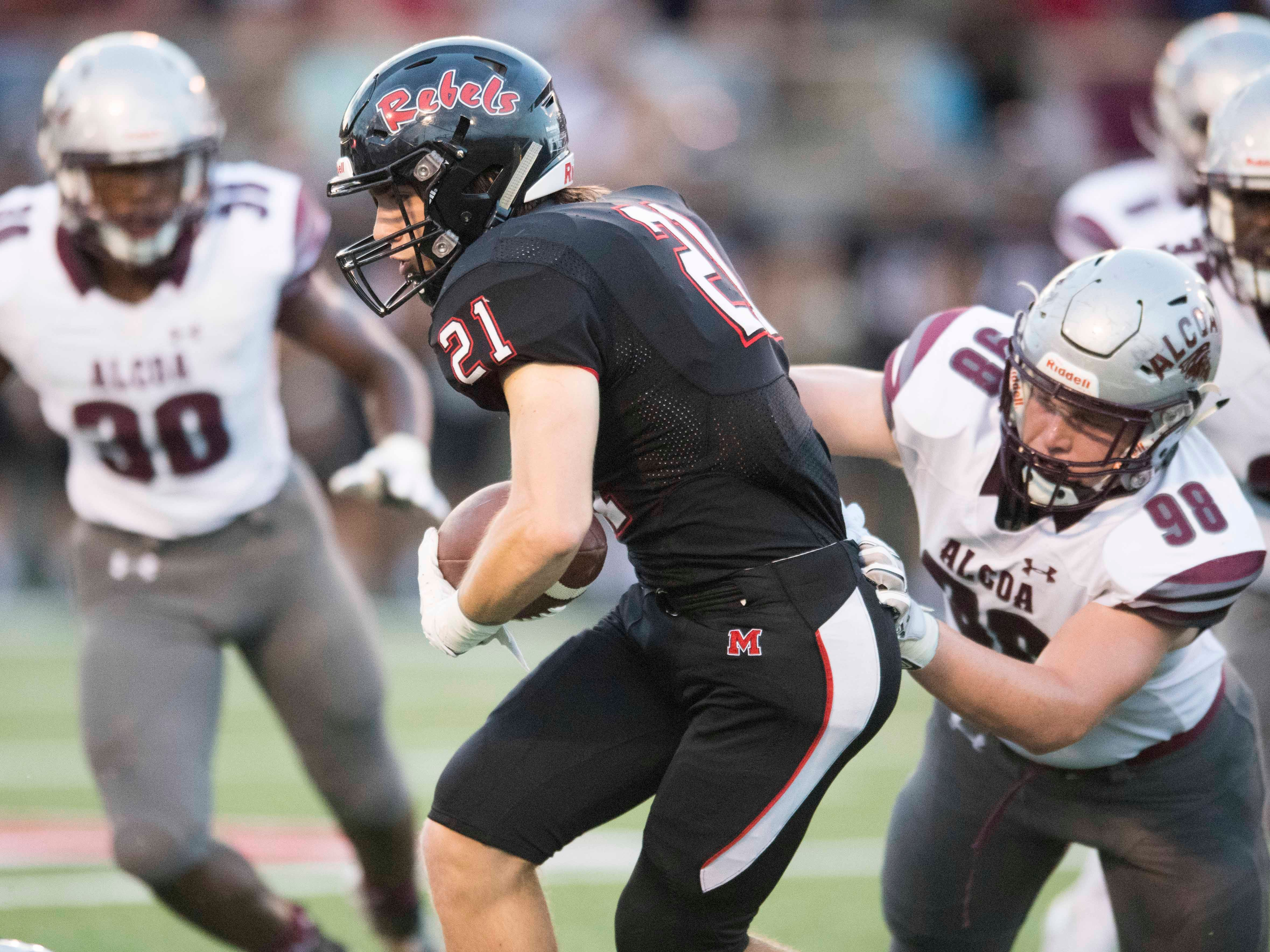Maryville's Bryson Teffeteller (21) is grabbed by Alcoa's Grey Carroll (98) in the football game at Maryville on Friday, September 7, 2018.