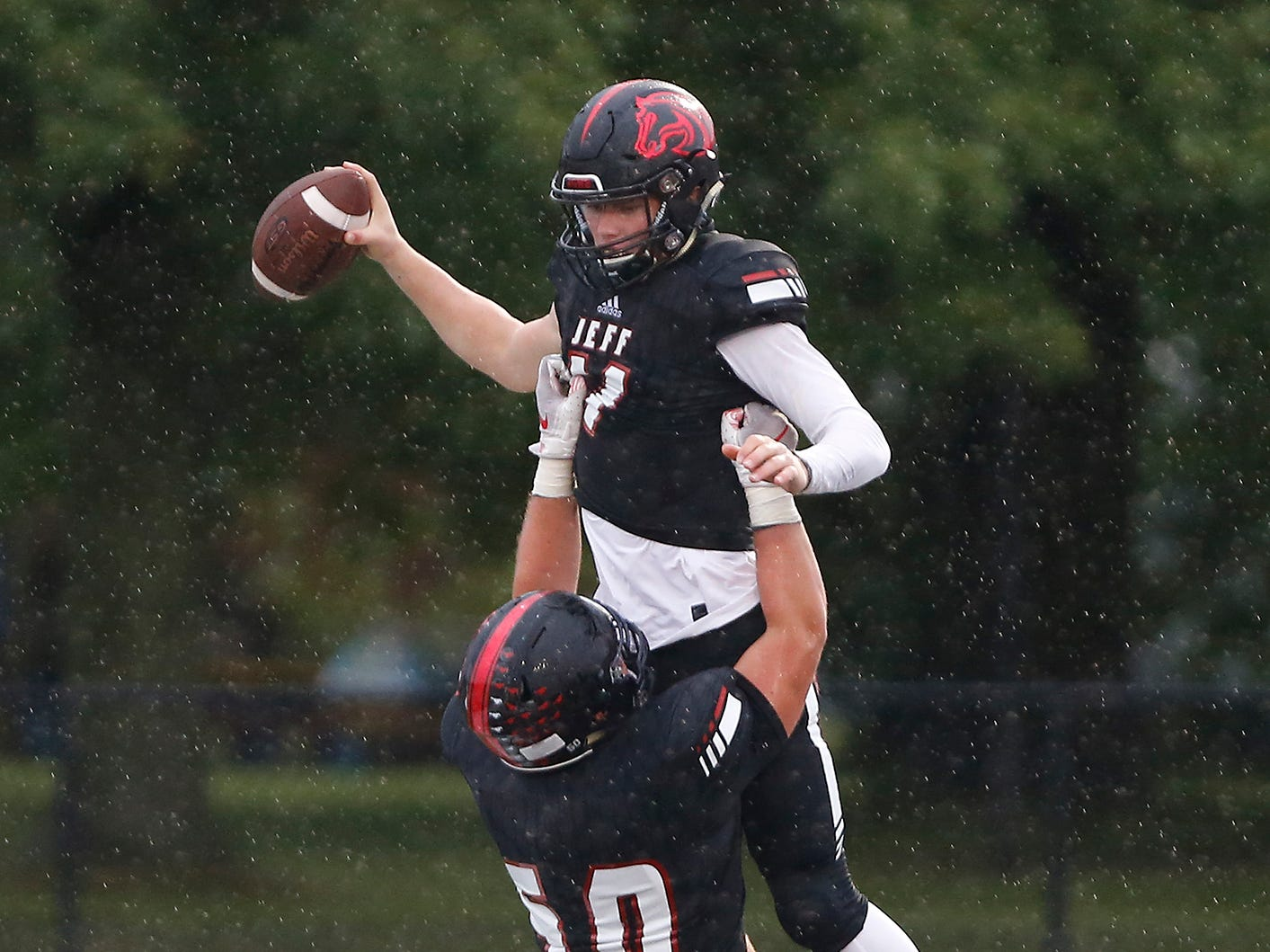 Lafayette Jeff quarterback Maximus Grimes is lifted into the air by teammate Colton Lehnen after his rushing touchdown at 9:48 in the first quarter against Harrison Friday, September 7, 2018, at Scheumann Stadium. Jeff defeated Harrison 31-14.