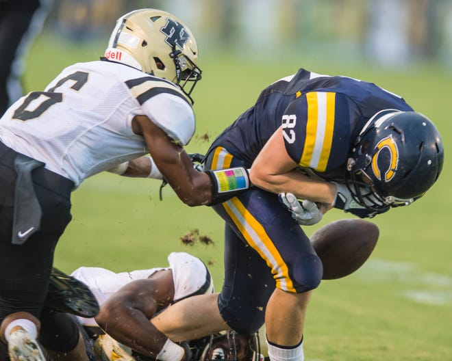 Carencro's Blake Lacombe (82) gets tackled and loses the ball against the New Iberia Yellow Jackets on Friday Sept. 7, 2018.