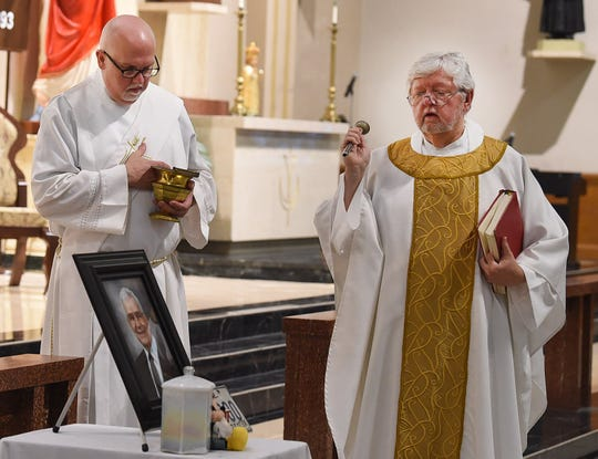 Monsignor Russell Harrington, right, bestows blessings during the funeral Mass for J.A. Allen Friday at St. Landry Catholic Church.