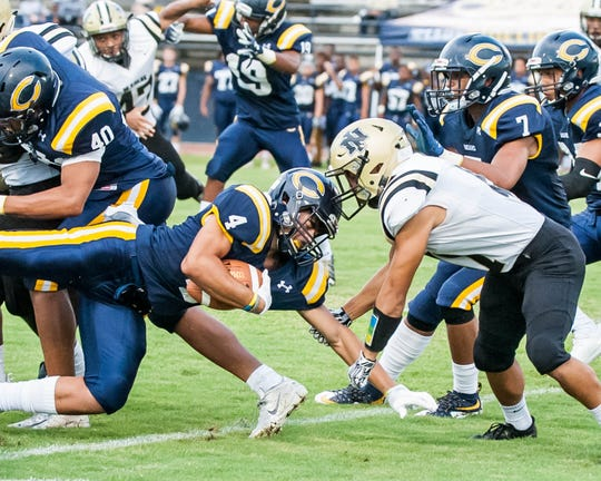 Carencro's Desmond Johnnie (4) goes  up the middle for the first down as the Bears play host to the NISH Yellow Jackets on Friday Sept. 7, 2018.