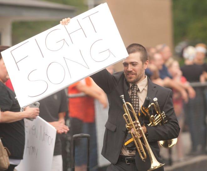 Fern Creek High School band director Josh Warren hoists a sign showing the next selection. Sept. 7, 2018