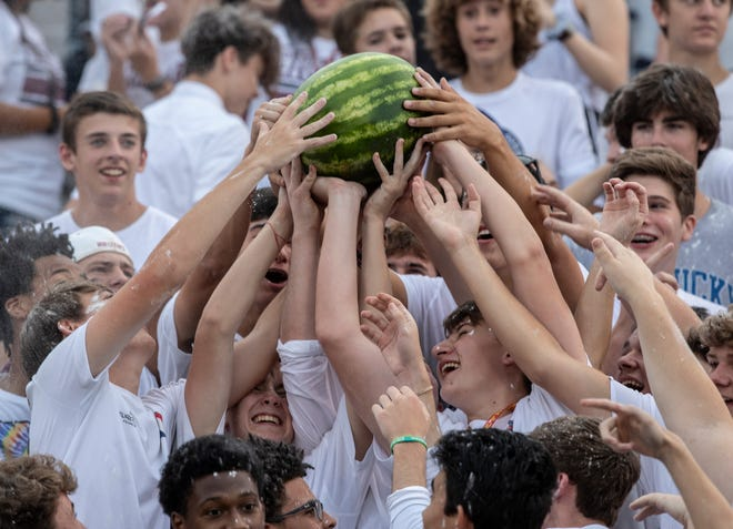 Ballard High students lifted a watermelon through the crowd during their team's game against Central. Sept. 6, 2018.