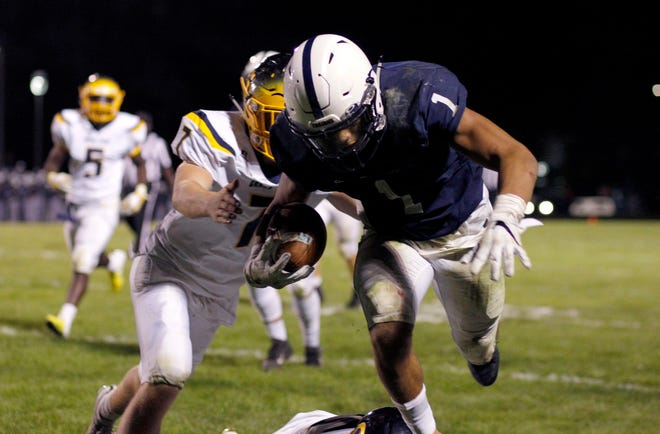 East Lansing's Kobe Hayward (1) is tripped up by Grand Ledge's Bear Nelson, left, and Mason Moore, Friday, Sept. 7, 2018, in East Lansing, Mich. East Lansing won 31-28.