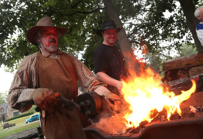 Bob Nobel works over a coal forge while Bryden Kinniard forms cast iron over an anvil in South Park on Saturday. The two were demonstrating blacksmithing skills for the 4th annual Living History Days. Visitors who braved the rains that day were treated to various skills such as knitting, while also viewing the inside of a block house.