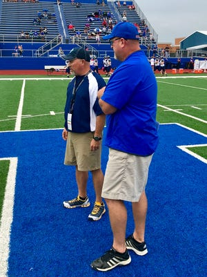 River Valley head football coach Doug Green, left, meets with his counterpart at Highland in Chad Carpenter before Friday night's game in Covrett Stadium. Highland won 41-8.