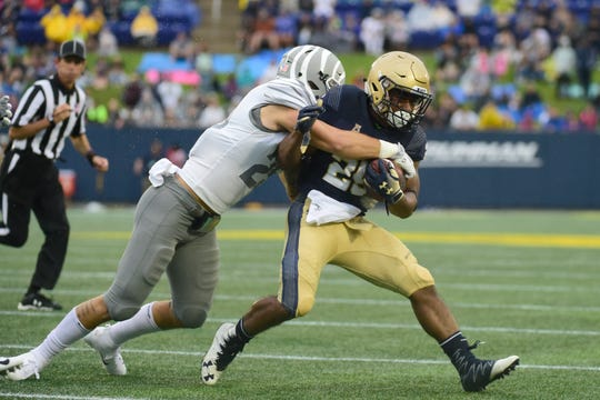 Memphis Tigers linebacker Austin Hall (25) tackles Navy Midshipmen tight end Tazh Maloy (25) during the first quarter at Navy-Marine Corps Memorial Stadium.