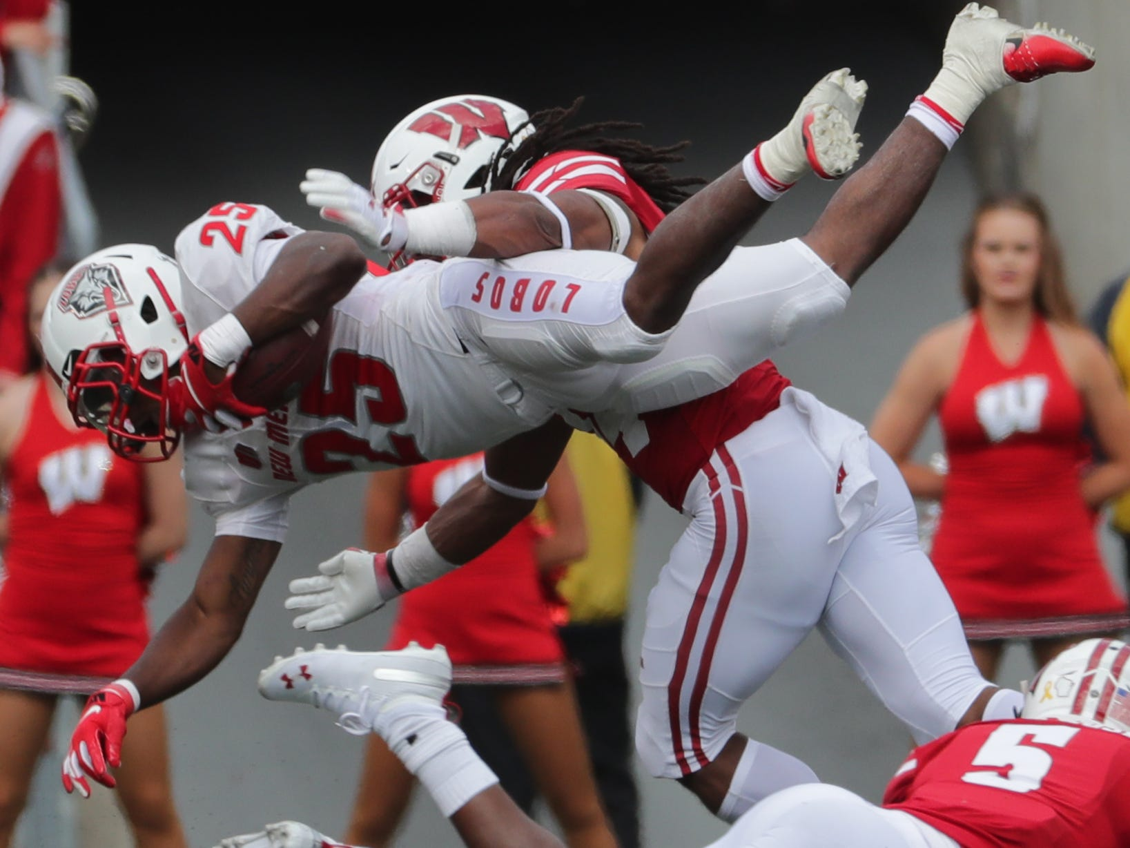 New Mexico running back Tyrone Owens goes airborne before being tackled by Wisconsin safety D'Cota Dixon.