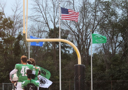 Flags fly in the wind as Greendale lines up for the national anthem prior to a game against New Berlin Eisenhower on Sept. 7.