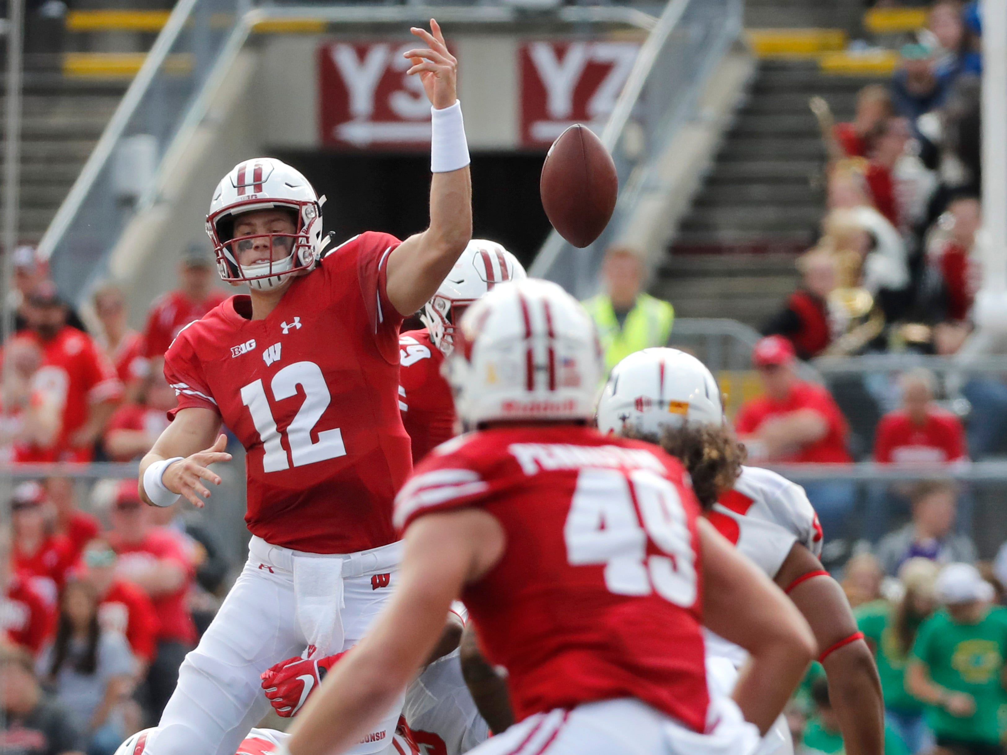 Wisconsin quarterback Alex Hornibrook  is tackled while throwing a pass that was intercepted by New Mexico linebacker Evahelotu Tohi.