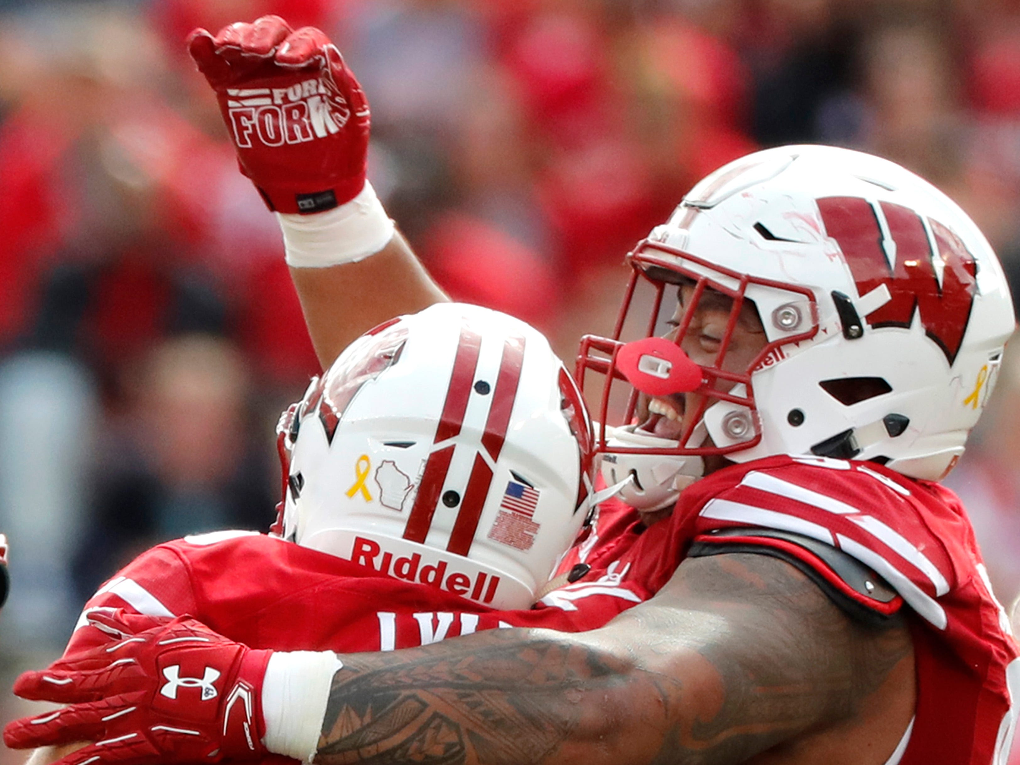 Wisconsin nose tackle Kayden Lyles celebrates with Wisconsin nose tackle Olive Sagapolu  after a fumble recovery.