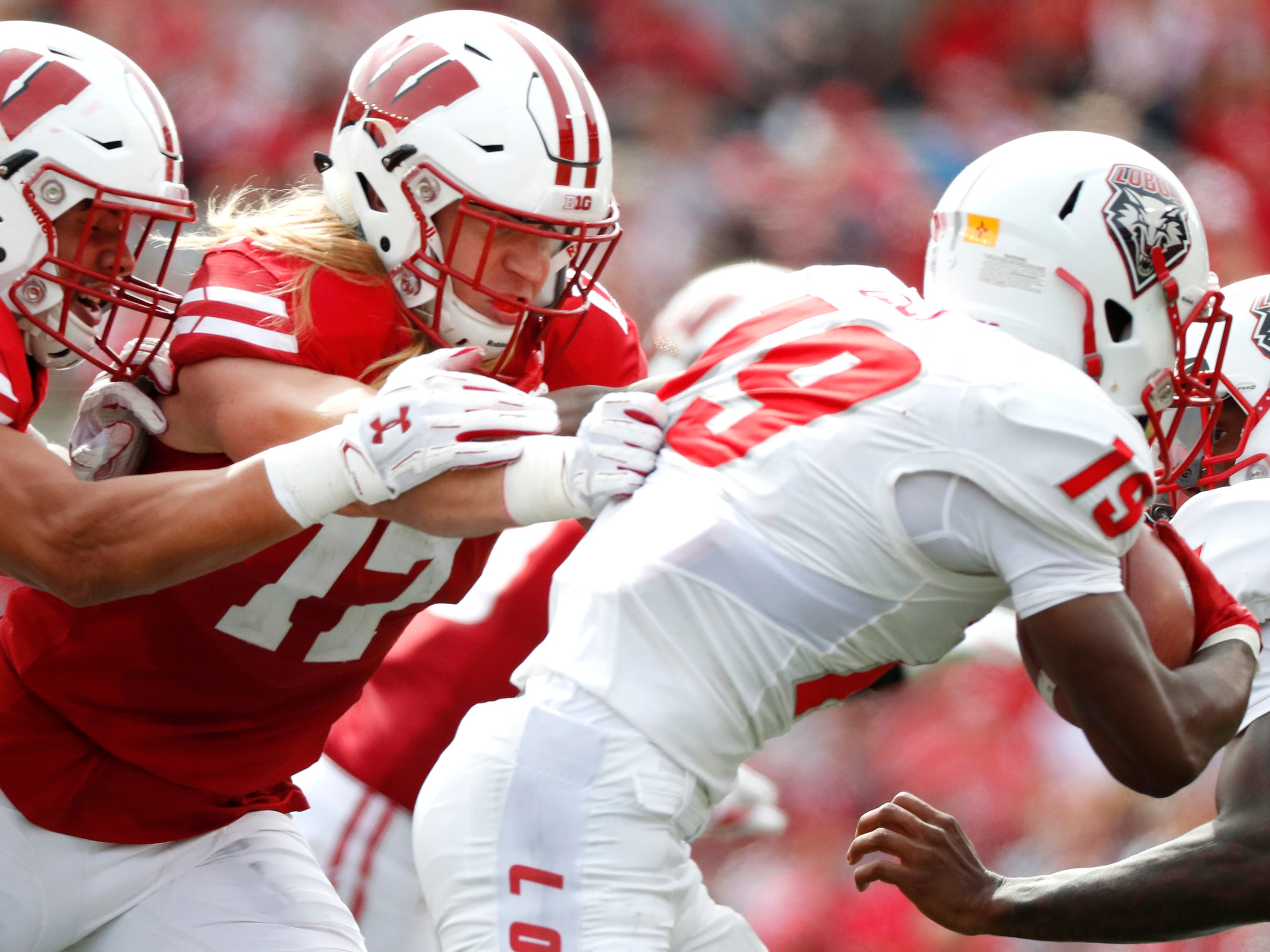 Wisconsin linebacker Zack Baun and Wisconsin linebacker Andrew Van Ginkel work to bring New Mexico wide receiver Elijah Lilly.