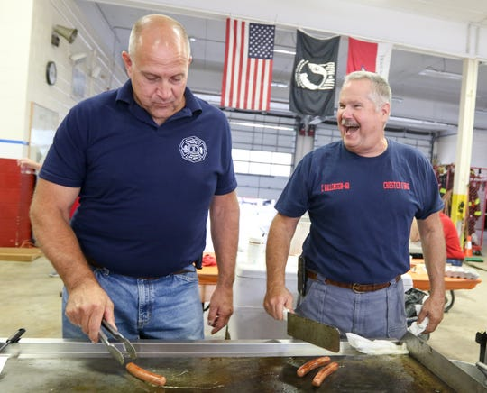 Scott Dilley and Craig Wallenstein of the Chester Fire Department share a laugh as they cook for the  Ladies Auxiliary fundraiser during the 45th annual Fall Craft Show in Chester on Saturday, September 8, 2018.