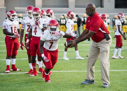 Lee head coach Tyrone Rogers hands the ball off to Tedarrian Murray (7) as they warm up before taking on Jeff Davis at Cramton Bowl in Montgomery, Ala., on Friday, Sept. 7, 2018. Lee defeated Jeff Davis 25-10.