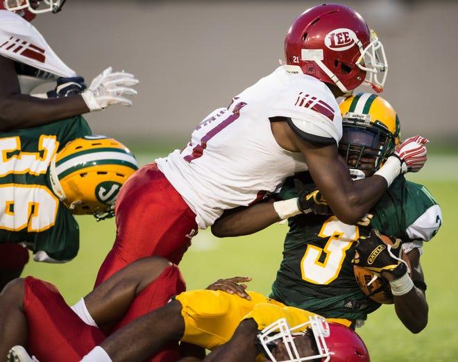 Lee's Len'darius Orum (21) takes down Jeff Davis' Terrence Reed  (3) at Cramton Bowl in Montgomery, Ala., on Friday, Sept. 7, 2018.