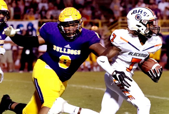 Blackman's Micaleous Elder (7) runs the ball as Smyrna's Dallas Walker (8) tries to bring him down during the game at Smyrna High School on Friday, Sept. 7, 2018.