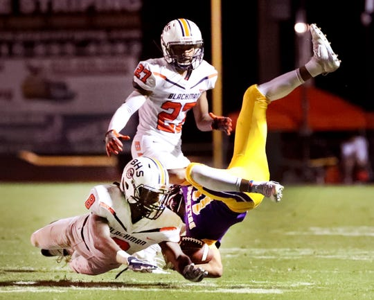 Smyrna's Tyler Lansden (11) flips upside down as he is tackled by takes on Blackman's Dajeun Gibson (8) during the game at Smyrna High School on Friday, Sept. 7, 2018. Blackman's Jalen Brown (27) gets ready to move in to assist with the tackle.