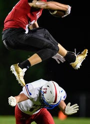 Ravenwood's Jake Briningstool (9) leaps over Page's Ryan Cannon (17) during the first half at Ravenwood High School in Brentwood, Tenn., Friday, Sept. 7, 2018.