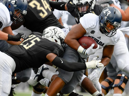 Nevada running back Kelton Moore (23) is tackled by Vanderbilt linebacker Josh Smith (25) during the first half at Vanderbilt University in Nashville, Tenn., Saturday, Sept. 8, 2018.