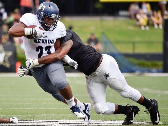 Nevada running back Kelton Moore (23) is tackled by Vanderbilt linebacker Josh Smith (25) during the first half at Vanderbilt University in Nashville, Tenn., Saturday, Sept. 8, 2018.