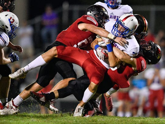 Page's Til Cheshire (8) is tackled by Ravenwood's Owen Davis (54) and Ben Severance (26) during the second half at Ravenwood High School in Brentwood, Tenn., Friday, Sept. 7, 2018.