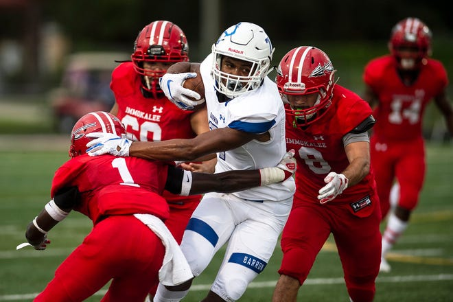 Barron Collier's Jayden Rolle push of a defender during a game against Immokalee High School in Immokalee, Fla. on Friday, September 7, 2018.