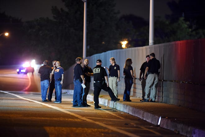 Investigators at the scene where a police officer on a motorcycle fired their service weapon after apparently being struck by a car they were attempting to stop on the Madison Avenue bridge over Interstate 80 in Paterson, NJ around 7:30 p.m. on September 7, 2018.
