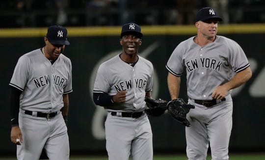 New York Yankees outfielders, from left, Aaron Hicks, Andrew McCutchen and Brett Gardner react at the end of the team's baseball game against the Seattle Mariners, Friday, Sept. 7, 2018, in Seattle. The Yankees won 4-0.