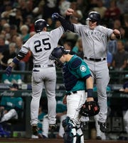 New York Yankees' Gleyber Torres, left, jumps to celebrate with Luke Voit, right, above Seattle Mariners catcher Mike Zunino after Torres hit a two-run home run to score Voit during the second inning of a baseball game Friday, Sept. 7, 2018, in Seattle.