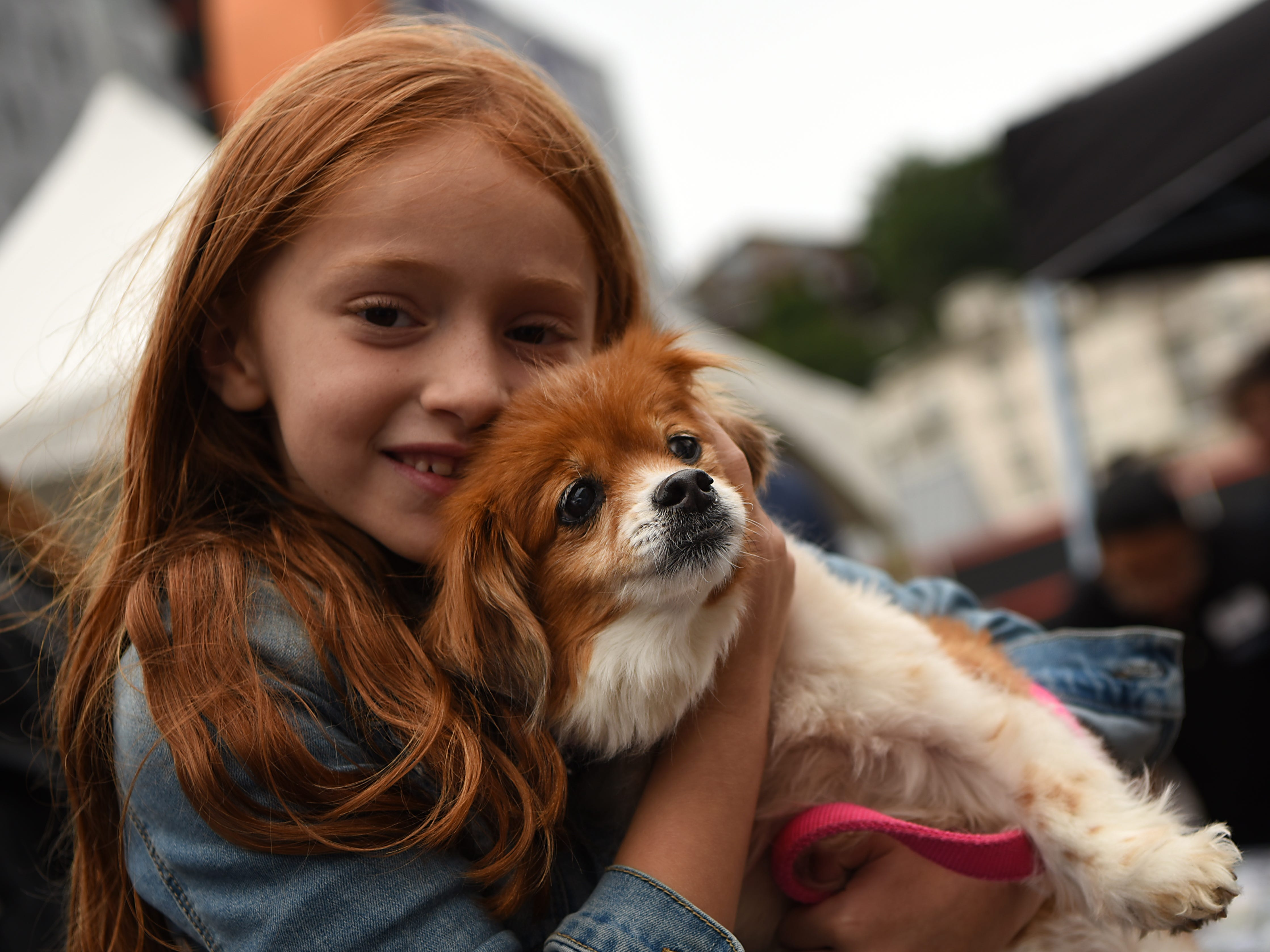 Emma Appel, six years old from Edgewater, holds Rosie Perez, a seven year old mixed breed, at Woofstock 2018, a benefit for Bergen County animal rescue organizations, at City Place in Edgewater on Saturday September 8, 2018.