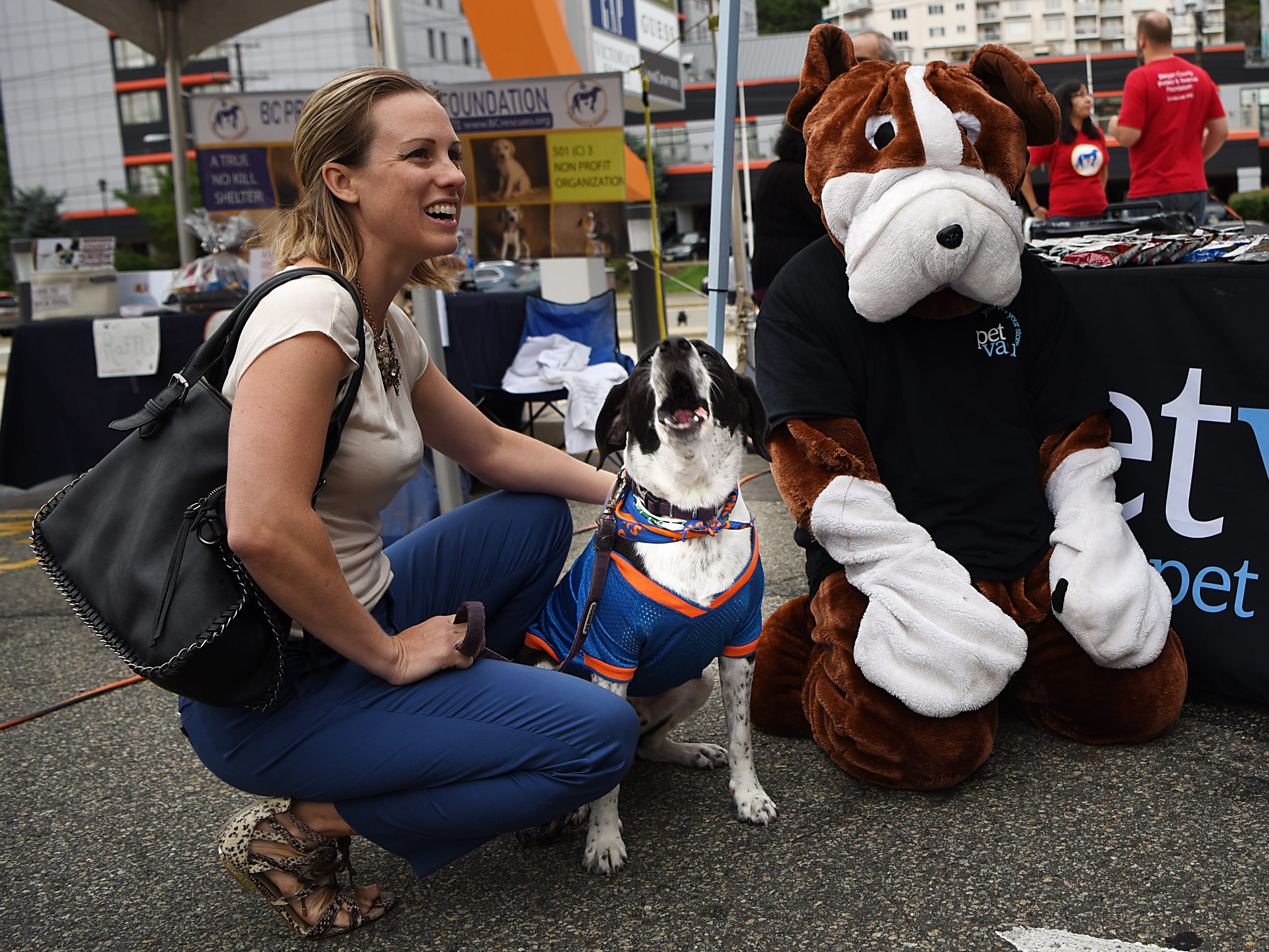 (From left) Erica Page and her dog Casey, five years old, pose for photos with the Pet Valu mascot. Woofstock 2018, a benefit for Bergen County animal rescue organizations, at City Place in Edgewater on Saturday September 8, 2018.