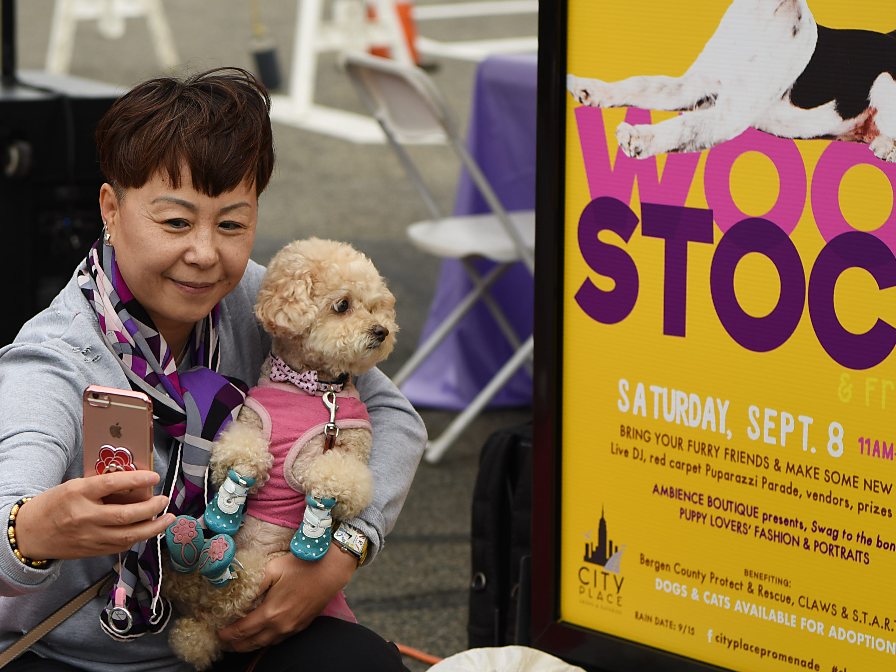 Chanel, a nine year old dog, gets a a photo taken in front of the Woofstock sign. Woofstock 2018, a benefit for Bergen County animal rescue organizations, at City Place in Edgewater on Saturday September 8, 2018.
