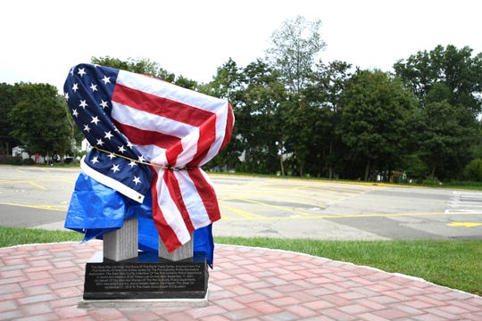 A recently installed 9/11 memorial that includes World Trade Center steel is covered by a tarp and a flag at Cedar Grove High School on Saturday, September 8, 2018.