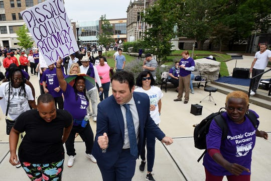 Paterson Mayor Andre Sayegh (center) dances the cupid shuffle prior to the start of the Passaic County Recovery Walk in Paterson on Saturday September 8, 2018.